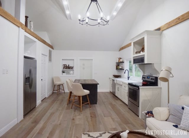 white kitchen, wood island, white beams, living room