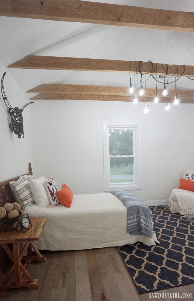 exposed beams in bedroom with vintage socket lights